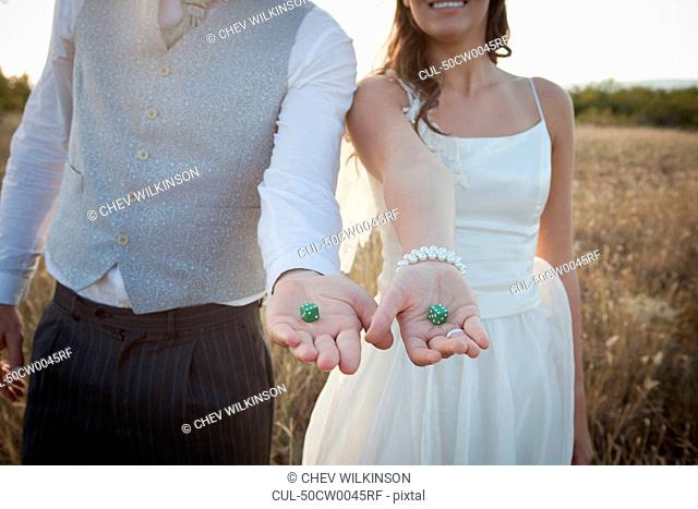 Newlywed couple holding green dice