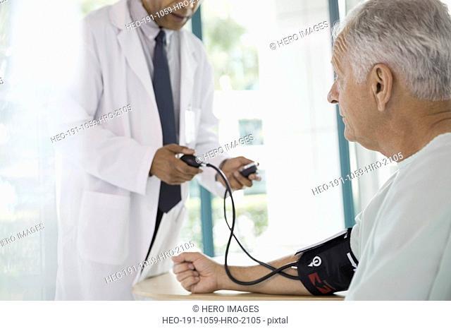 Male doctor measuring blood pressure