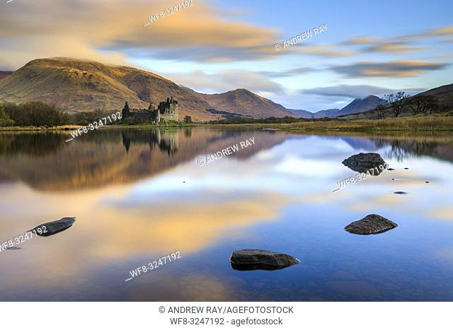 Kilchurn Castle and it's mountainous snow capped backdrop reflected on the still surface of Loch Awe in Argyll and Bute, Scotland