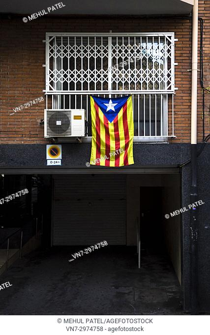 Pro-Catalan indepence flag hanging outside an apartment window with shutters in Barcelona - Catalonia, Spain, Europe