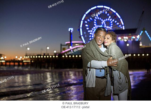 Couple hugging on beach at night