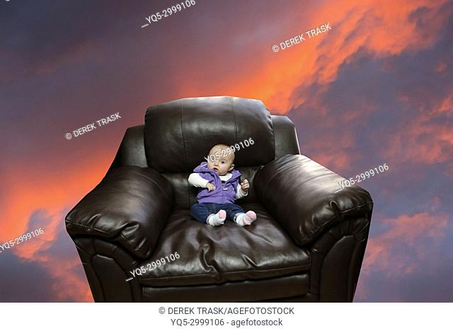 girl child sitting in oversize armchair looking concerned