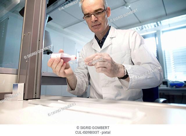 Male meteorologist preparing microscope slide in weather station laboratory