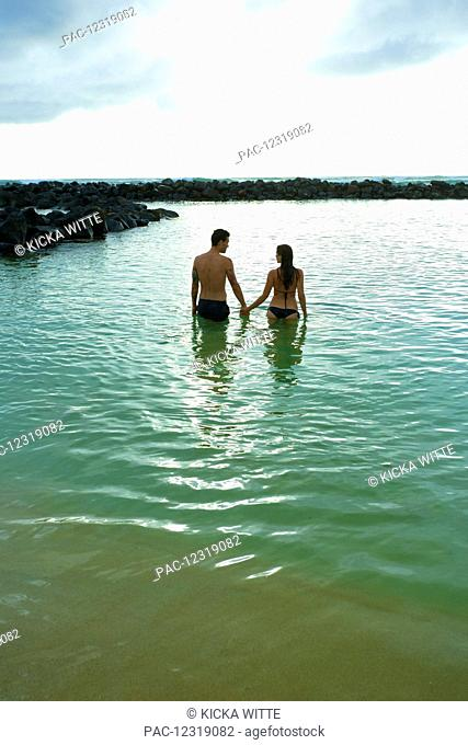 A couple holds hands and walks into the ocean off Lydgate Beach; Kauai, Hawaii, United States of America