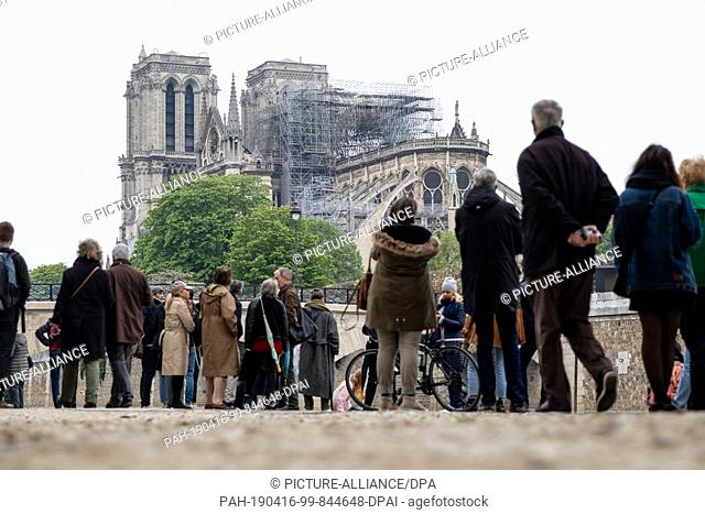 16 April 2019, France (France), Paris: Numerous people look to the cathedral Notre-Dame. A fire broke out in the world-famous cathedral Notre-Dame in Paris on...