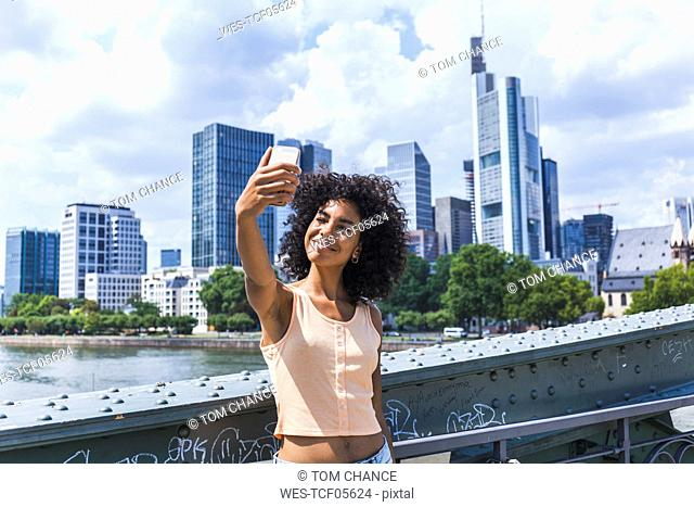 Germany, Frankfurt, portrait of content young woman with curly hair taking selfie in front of skyline