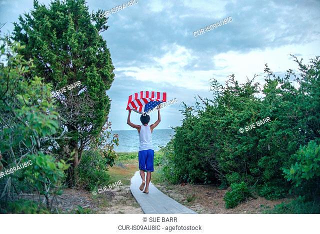 Rear view of boy holding up American flag on coastal path, Cape Cod, Massachusetts, USA