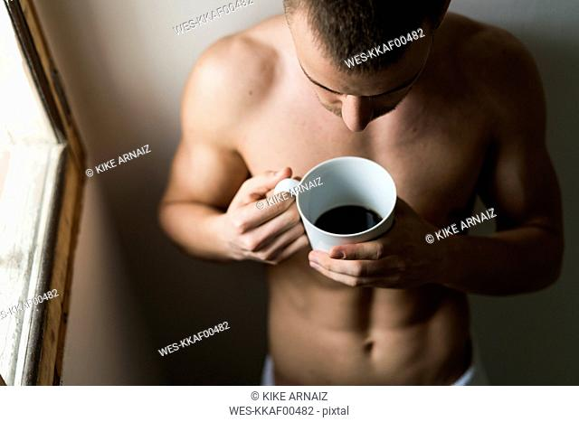 Attractive young amn with six pack drinking coffee