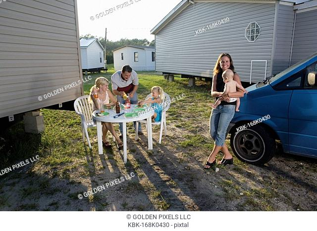 Blue collar families enjoying a cookout in front of trailer home