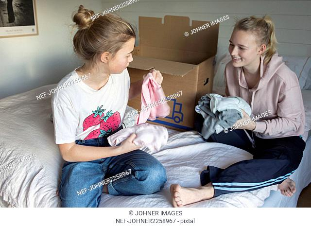 Teenage girls packing clothes into moving box
