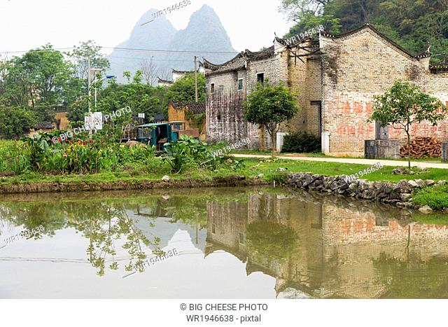 Karst mountains and temple reflected in a village rice paddy, Yangshuo, China