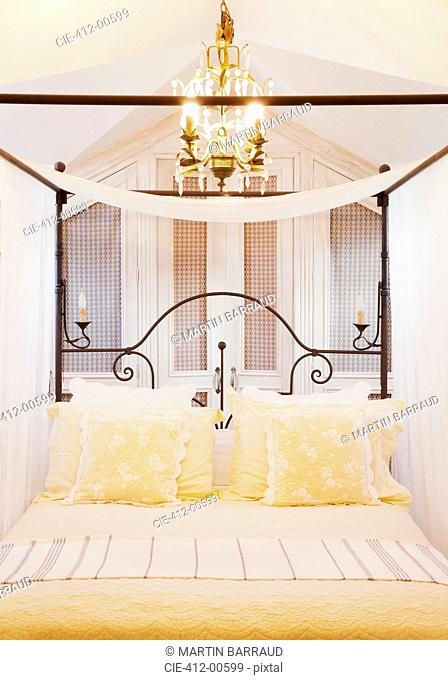 Chandelier over four poster bed with yellow linens