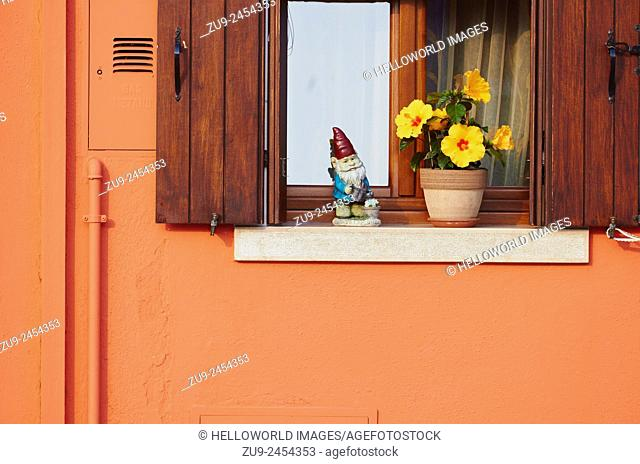 Gnome and flowers on windowsill of orange painted house, Burano, Venetian Lagoon, Veneto, Italy, Europe