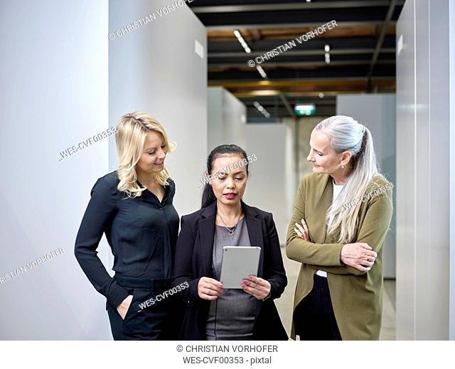 Three businesswomen sharing tablet on office floor