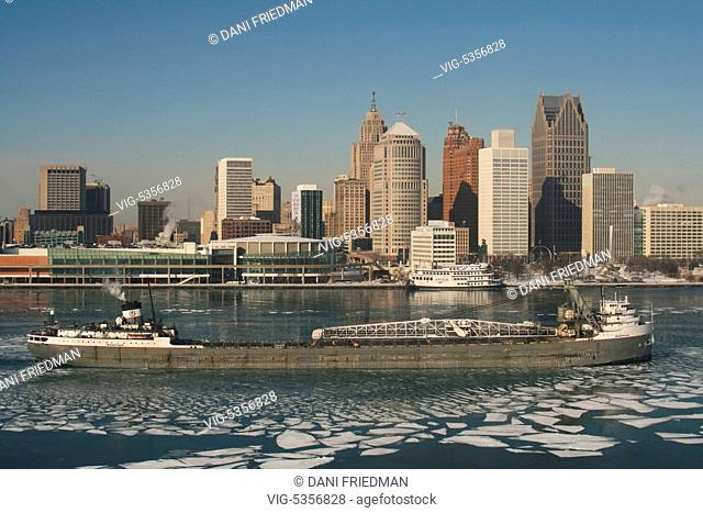 A large bulk carrier cargo ship travels along the Detroit River with the skyline of downtown Detroit, Michigan, USA in the background