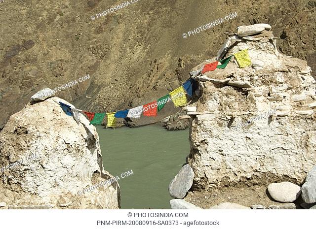 Prayer flags hanging on chortens at a river bank, Indus River, Ladakh, Jammu and Kashmir, India