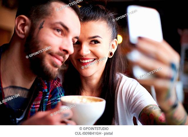 Couple in cafe taking selfie