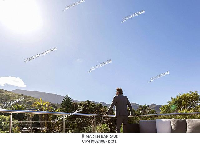 Businessman standing on balcony patio below sunny blue sky
