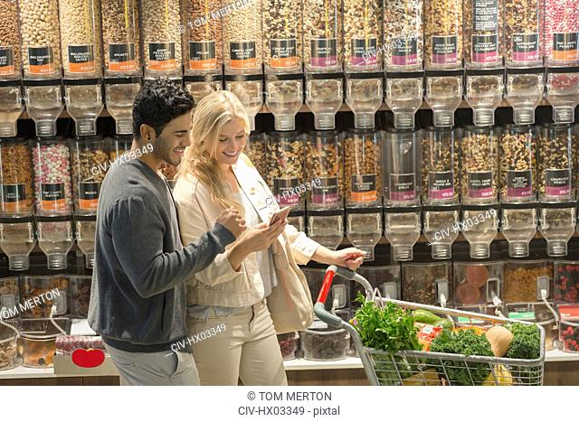 Young couple using cell phone, grocery shopping in market