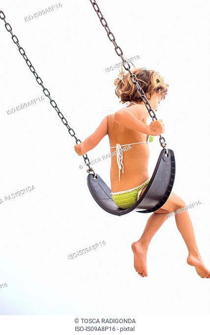 Back view of girl in swimsuit on swing