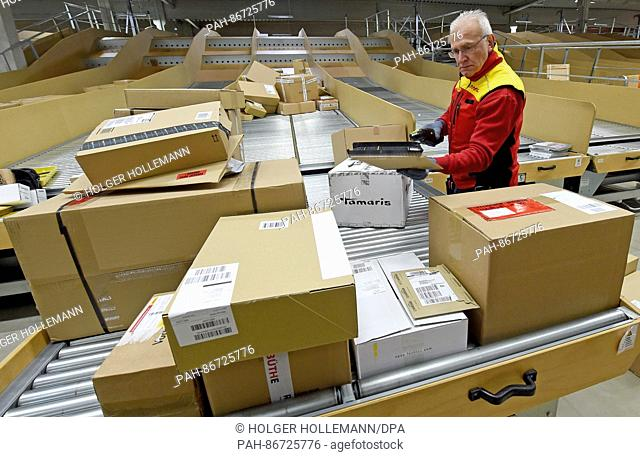 Package deliverer Hans-Joachim Harnagel reads the code on a package with a scanner at the DHL delivery base Braunschweig, Germany, 21 December 2016