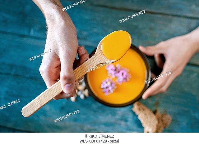 Close-up of man's hands eating creamed pumpkin soup