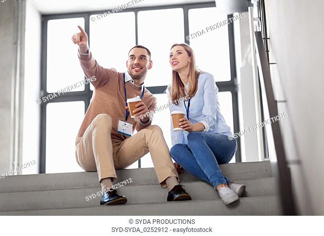 man and woman with conference badges drink coffee