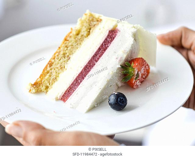 A slice of white chocolate mousse cake with strawberries and coconut