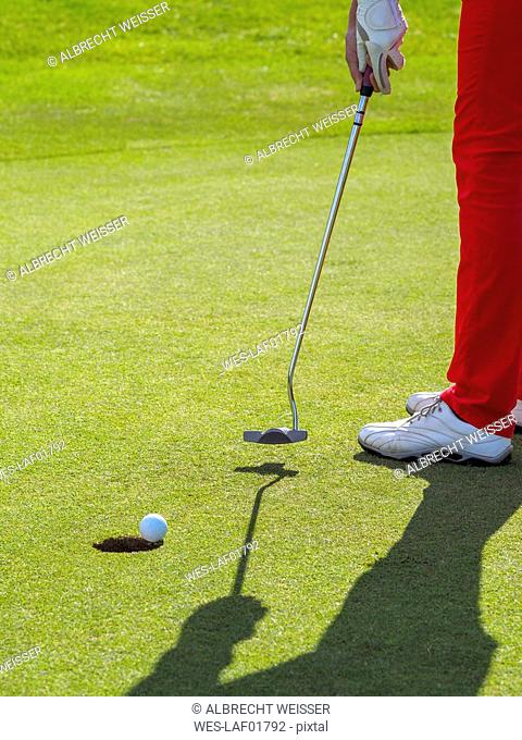 Golfer on golf course, partial view
