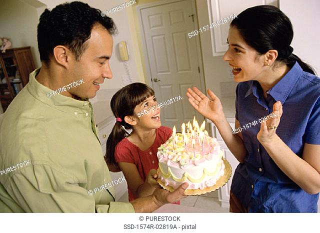 Girl standing in front of a birthday cake with her parents