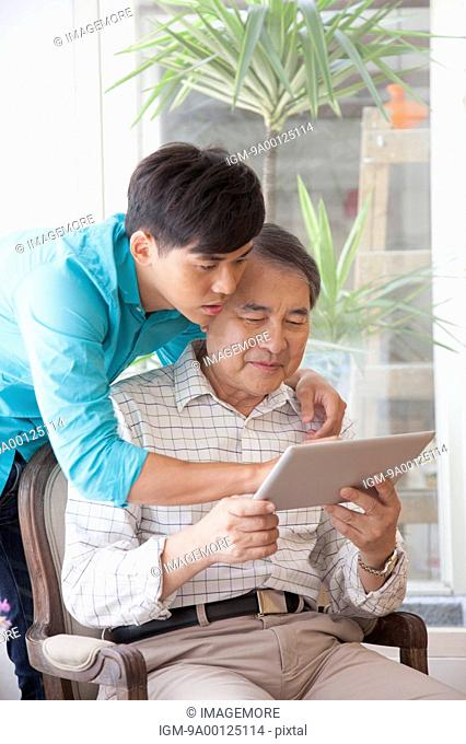Family with one child holding touchpad and looking down together