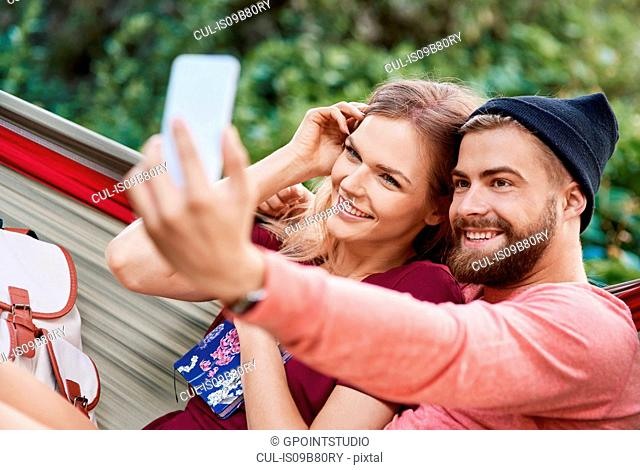 Couple in hammock taking selfie smiling, Krakow, Malopolskie, Poland, Europe