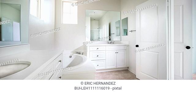 View of a contemporary white bathroom with bath; sink and mirror at home; Ontario; California; USA