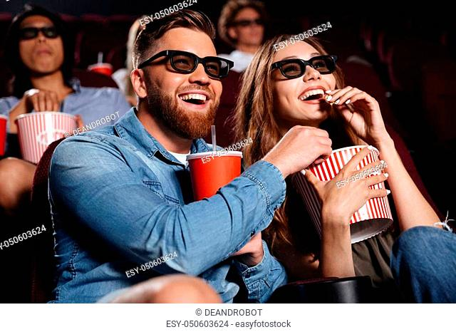 Picture of happy friends sitting in cinema watch film eating popcorn and drinking aerated sweet water
