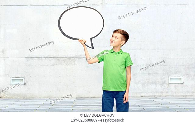 childhood, communication, advertisement and people concept - happy smiling boy in green polo t-shirt holding blank white text bubble banner over urban street...