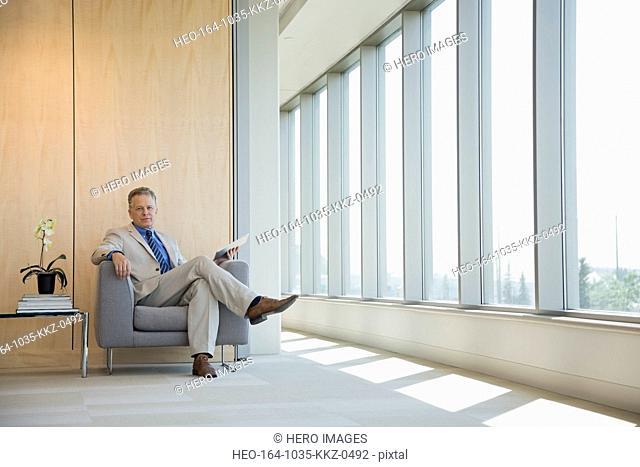 Portrait of businessman sitting in chair