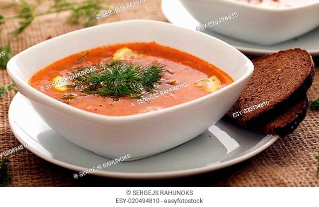 Image of bowls of hot red soup served with bread