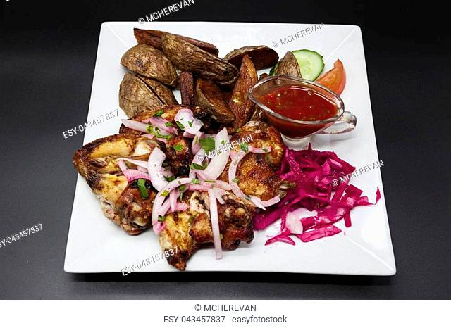 Fried chicken wings with spicy sauce, potatoes on a plate on black background. Fried chicken wings grilled on a plate with spicy onions and red cabbage and...