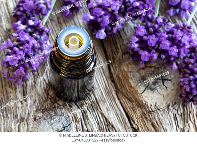 A bottle of essential oil with fresh blooming lavender on a rustic wooden background