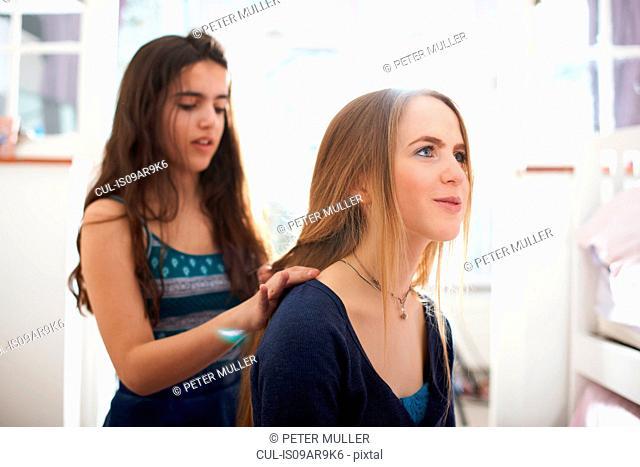 Teenage girl having hair plated by best friend in bedroom