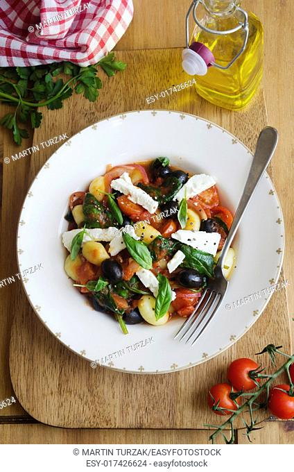 Gnocchi with feta, black olives and cherry tomatoes topped with basil
