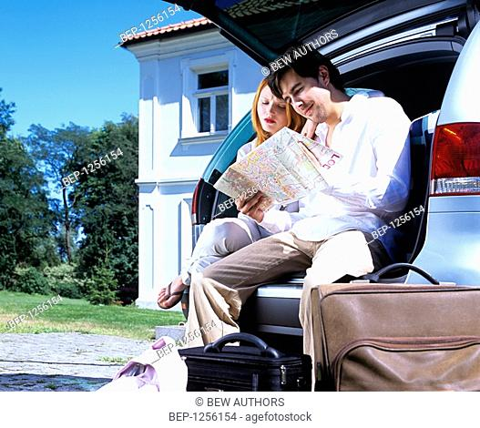 Couple sitting in a car boot and reading a map