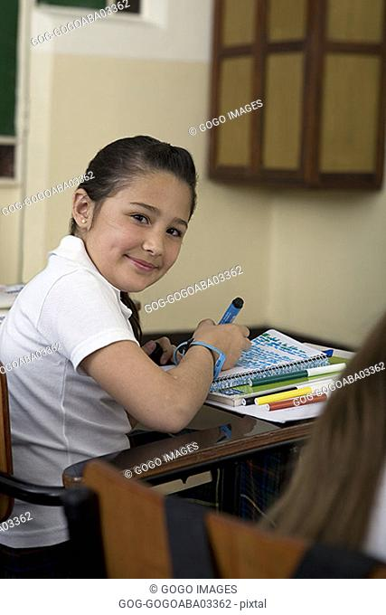 Young student sitting at desk in class