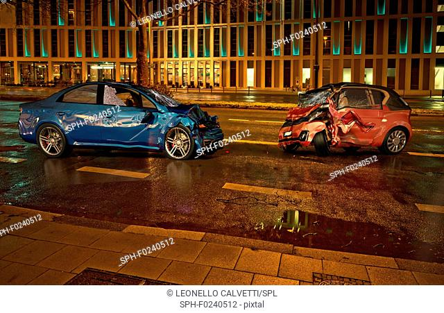 Two cars accident. Crashed cars on the road on city location at night time. A blue sedan against a red city car. Frontal collision with big damages