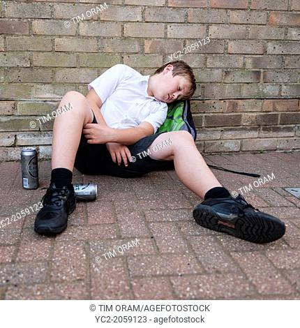 A boy of 10 in his school uniform drinking lager alcohol showing the affect of underage drinking in the Uk