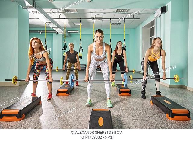 Full length of trainer with determined women lifting barbell during step aerobics