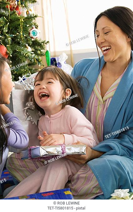 Mother and daughters 10-11 unwrapping christmas gifts