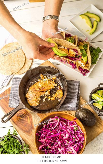 Woman preparing tortilla with tilapia, avocado and red cabbage
