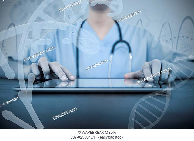 Composite image of mid-section of female doctor using digital tablet