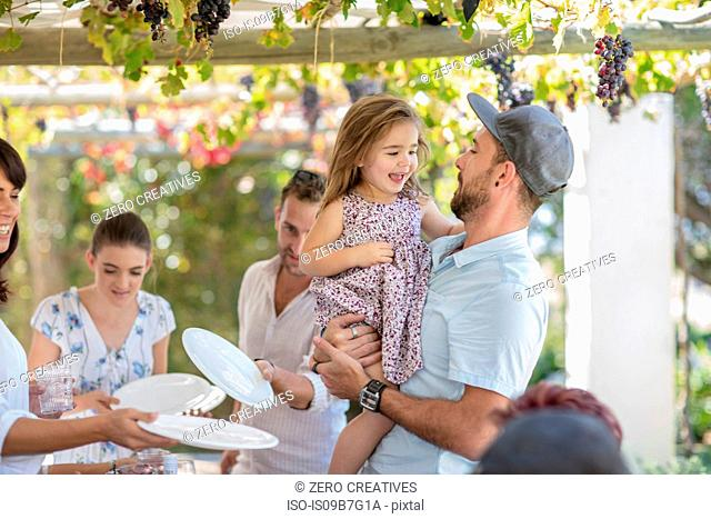Man and girl at outdoor family lunch